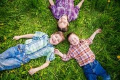 3 дет на траве с одуванчиками Стоковые Фото