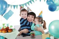 2 дет обнимая их мать на таблице партии Стоковые Изображения RF