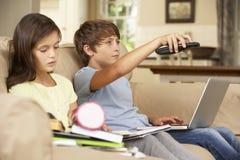 2 дет отвлеченного телевидением пока пробующ для того чтобы сделать с домашней работой Стоковое Изображение