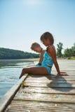2 дет охлаждают вниз их ноги в озере в лете Стоковая Фотография RF
