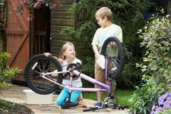 2 дет очищая велосипед совместно Стоковая Фотография