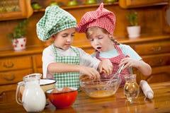 2 дет подготавливая яичка для печений в кухне Стоковые Изображения RF