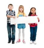 3 дет при открытые рти держа пустой лист бумаги Стоковое Изображение RF