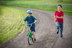 2 дет путешествуя вместе с его велосипедом на сельском ландшафте Стоковая Фотография RF
