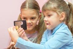 2 дет рассматривали монетку через лупу Стоковое Фото