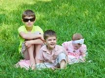 3 дет сидят в траве, играющ и имеющ потеху Стоковое Фото