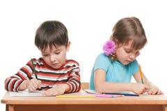 2 дет пишут на столе Стоковая Фотография RF