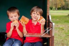 2 дет, сидящ в приюченном стенде, есть сандвичи Стоковое Фото
