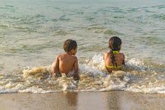 2 дет сидя на береге пляжа Стоковое Фото