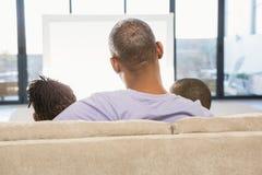 2 дет сидя на софе с их отцом Стоковое Фото