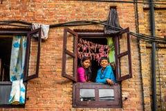 2 дет смотря из окна в Непале Стоковая Фотография