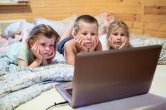 3 дет смотря компьтер-книжку пока в кровати Стоковые Изображения RF