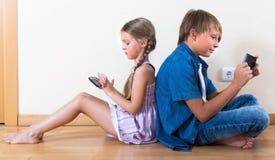 2 дет смотря к экрану smartphone Стоковые Фото