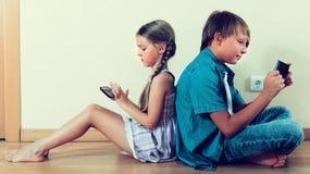 2 дет смотря к экрану smartphone Стоковое фото RF