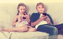 2 дет смотря к smartphones на софе Стоковое Фото