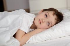 7 лет старого мальчика отдыхая в белой кровати с глазами раскрывают Стоковые Изображения RF