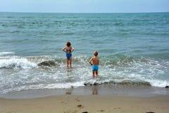 2 дет стоят в воде на пляже и смотрят море Стоковые Фотографии RF