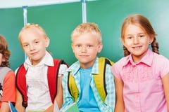3 дет стоят совместно перед классн классным Стоковые Изображения RF