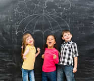 3 дет стоя под вычерченным зонтиком Стоковое фото RF