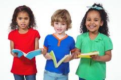 3 дет стоя с книгами в их руках Стоковые Фото