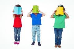 3 дет стоя с книгами перед их сторонами Стоковая Фотография RF