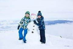 2 дет, строя снеговик na górze горы Стоковые Изображения RF