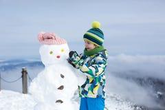 2 дет, строя снеговик na górze горы Стоковые Фотографии RF