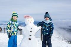 2 дет, строя снеговик na górze горы Стоковые Фото