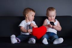 2 дет с мобильными телефонами на дате Стоковые Изображения