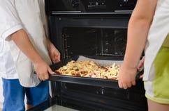 2 дет устанавливая домодельные пиццы в печи Стоковое Изображение