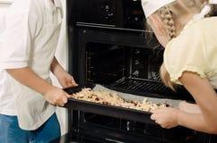 2 дет устанавливая домодельные пиццы в печи Стоковое Фото