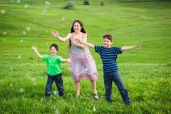 3 дет улавливают пузыри мыла на лужайке Стоковые Фотографии RF