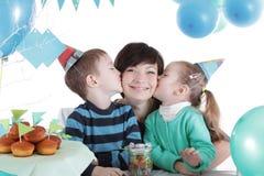 2 дет целуя их мать на таблице партии Стоковое Фото