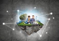 2 дет школьного возраста с книгой исследуя этот большой мир Стоковые Фотографии RF