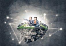 2 дет школьного возраста с книгой исследуя этот большой мир Стоковое фото RF