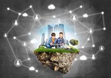 2 дет школьного возраста с книгой исследуя этот большой мир Стоковая Фотография