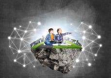 2 дет школьного возраста с книгой исследуя этот большой мир Стоковое Изображение