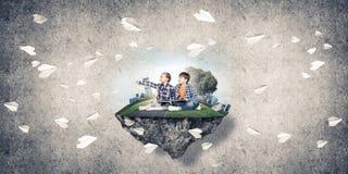 2 дет школьного возраста с книгой исследуя этот большой мир Стоковое Изображение RF
