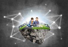 2 дет школьного возраста с книгой исследуя этот большой мир Стоковые Изображения