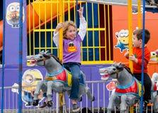Ехать брата и сестры веселый идет лошади круга Стоковое Фото