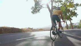 Ехать велосипедиста горного велосипеда гористый вдоль дороги изолированная белизна вид сзади field вал движение медленное сток-видео