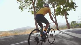 Ехать велосипедиста горного велосипеда гористый вдоль дороги изолированная белизна вид сзади field вал движение медленное акции видеоматериалы