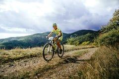 Ехать велосипедиста всадника женщины гористый на предпосылке гор и облаков Стоковые Фото