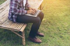 деятельность человека компьтер-книжки против предпосылки голубые облака field wispy неба природы зеленого цвета травы белое Стоковая Фотография RF