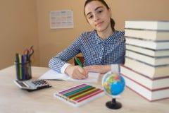 делающ девушку ее домашняя работа Концепция образования - книги на столе в аудитории Стоковые Фото