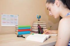 делающ девушку ее домашняя работа Концепция образования - книги на столе в аудитории Стоковое Фото