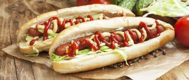 Еда горячей сосиски с сосисками, соусом мустарда и кетчуп Стоковое Изображение