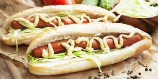 Еда горячей сосиски с сосисками, соусом мустарда и кетчуп Стоковая Фотография