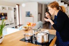 Еда дегустации домохозяйки будучи деланным в кухне Стоковое Изображение