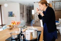 Еда дегустации домохозяйки будучи деланным в кухне Стоковые Изображения RF